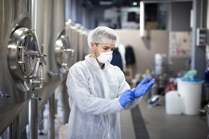 Man wearing chemical safety apparel or PPE, including a mask, gloves and a lab coat.